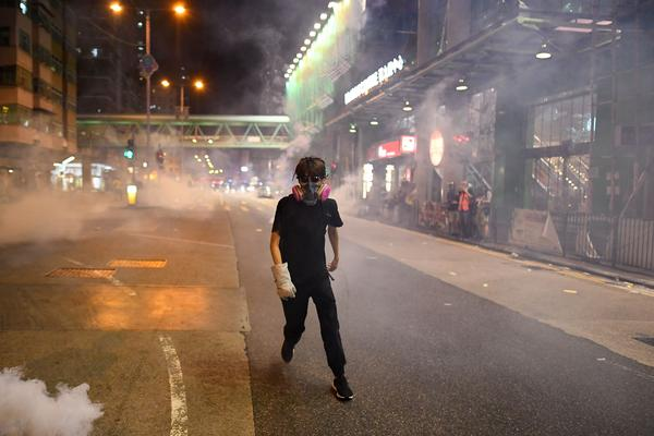 Pro-democracy protesters run away after police fired tear-gas shells in the Sham Shui Po area of Hong Kong.