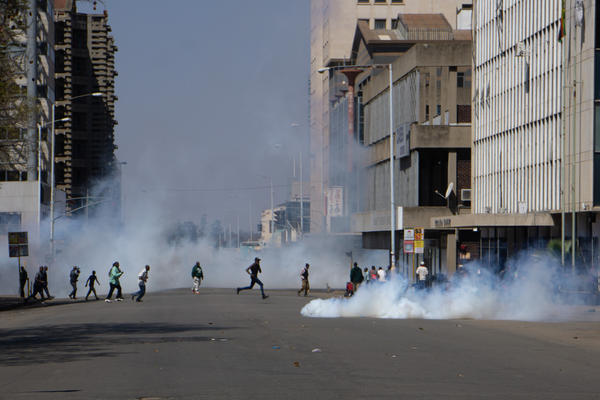 Protesters run from tear gas on Friday in Harare, Zimbabwe's capital.