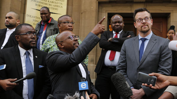 Nelson Mandela Foundation CEO Sello Hatang points to South Africa's current flag as he welcomes a ruling against its old flag in Johannesburg Wednesday. At right is Ernst Roets, leader of the AfriForum group that was targeted in the foundation's lawsuit.