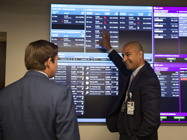 The 8,000-square-foot CareComm command center uses computers and artificial intelligence apps to display patient information, room availability and other information on a wall of video screens.