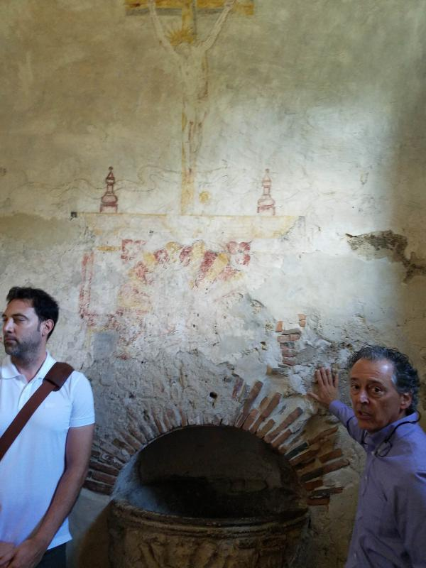 A water-damaged fresco in Mission Concepción's baptistry. Antonio Martinez-Molina, left; William DuPont, right.