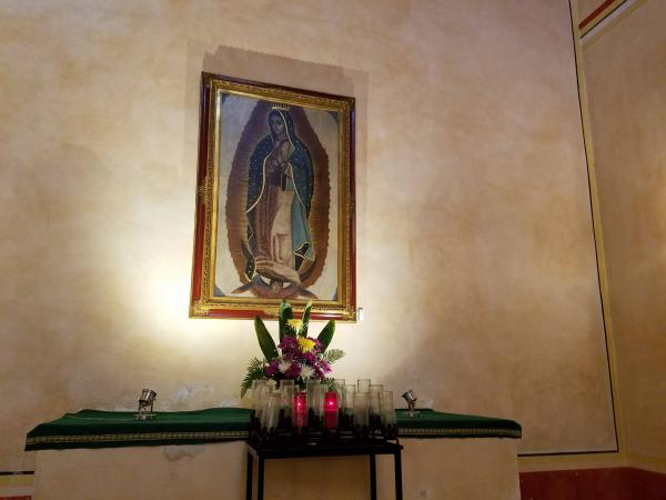 Oil painting of the Virgin de Guadalupe. This and other art works are at risk of damage from water and humidity. On the Feast of the Assumption of Mary, the painting is illuminated by a ray of sunlight.