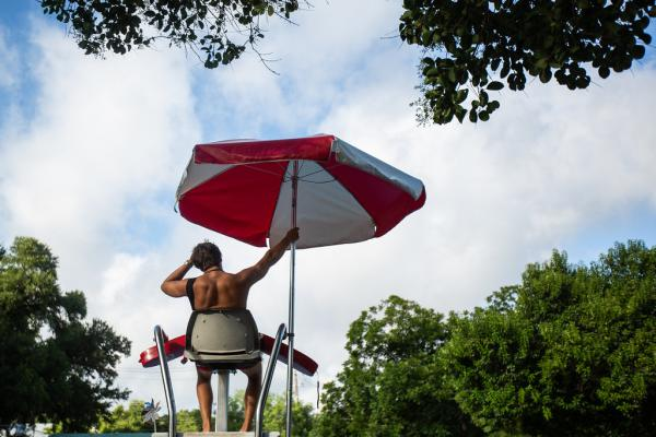 Quinlin Taylor watches swimmers at Big Stacy Pool in South Austin last month.