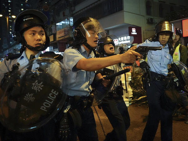 Police pull out their guns after a confrontation with demonstrators during a protest in Hong Kong on Sunday. One officer fired a warning shot in the air — the first such incident in 11 weeks of protests.