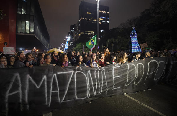 "Demonstrators march on Friday in São Paulo, Brazil, holding a banner with a message that reads in Portuguese: ""The Amazon belongs to the people."" Brazilians staged protests across the country throughout the weekend demanding action to combat the fires in the Amazon."