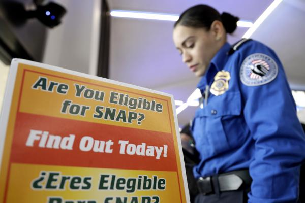 A Transportation Security Administration employee stands at a booth to learn about a food stamp program at a food drive at Newark Liberty International Airport, on Jan. 23, 2019, in Newark, N.J. A number of new rules and actions proposed by the Trump administration could affect poor or low-income people who use government safety net programs.