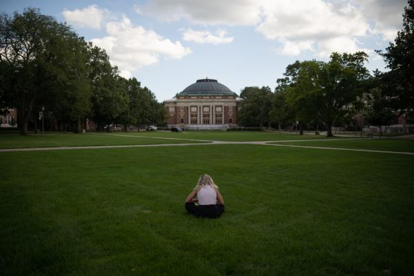 A person sits on the quad of the University of Illinois at Urbana-Champaign.