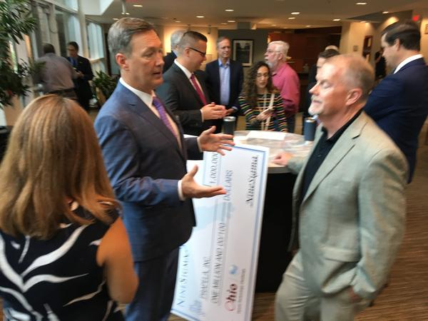 Ohio Opioid Technology Challenge winner John Konsin of Prapela (left)talks with others after the announcement of his company's win.