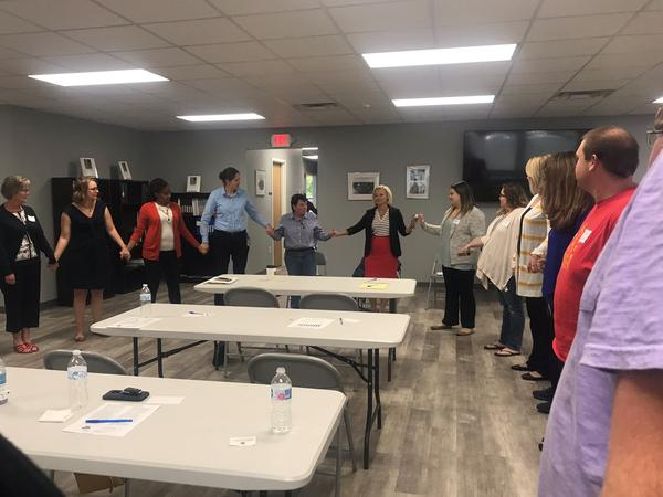 Children's Home Society Regional Director Brandi Davis leads participants of a foster care forum in a trust activity.