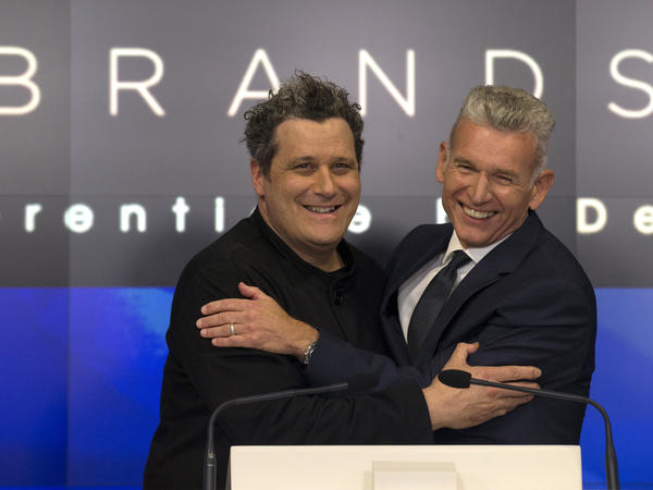 Designer Isaac Mizrahi (left) embraces Robert D'Loren, CEO of Xcel Brands, which once manufactured 70% of its clothes in China. Today that's down to about 20%. The company now manufacturers in a variety of countries, including Indonesia, India and Sri Lanka.