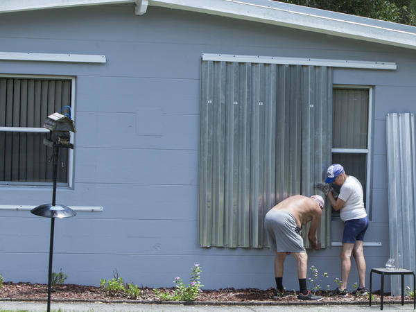 People in Vero Beach, Fla., install shutters on a home on Thursday in preparation for Hurricane Dorian. The storm reached Category 3 status on Friday and is expected to be Category 4 when it hits the U.S. coastline.