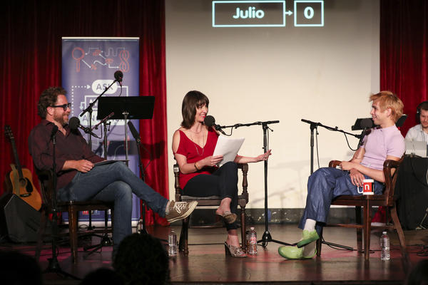Jonathan Coulton and Ophira Eisenberg lead a game with Julio Torres on <em>Ask Me Another</em> at the Bell House in Brooklyn, New York.