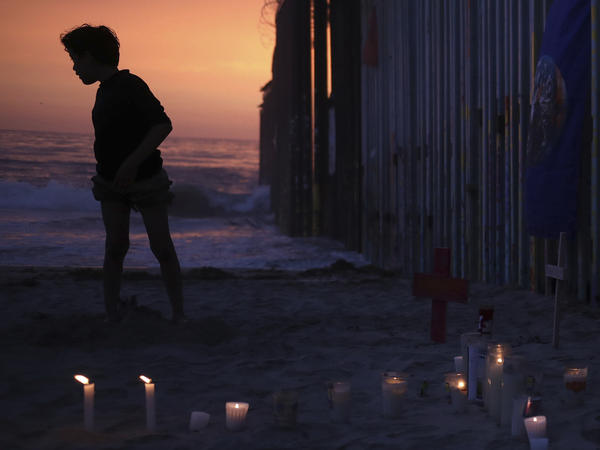 A youth stands Sunday by the border fence that separates Mexico from the U.S., where candles and crosses stand in memory of the father and daughter who died during their journey toward the U.S.