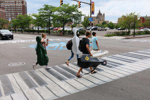 Musicians walk on a crosswalk painted like a piano outside the Eastman School of Music in Rochester, N.Y. Increasingly, urban designers and transportation planners say this kind of art — colorful crosswalks and engaging sidewalks — leads to safer intersections, stronger neighborhoods and better public health.