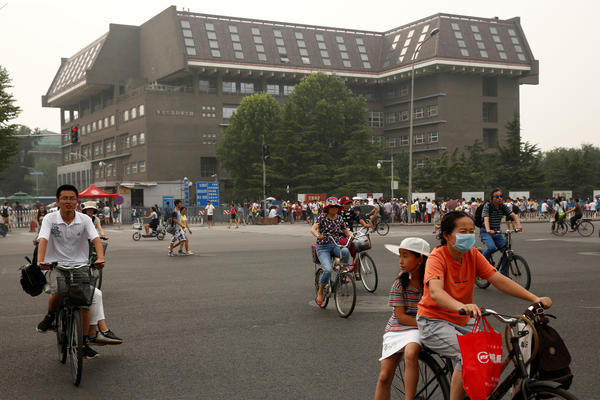 People cycle past a building at Peking University in Beijing in 2016. The university hosts Yenching Academy, a prestigious graduate studies program.