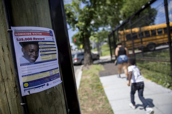 A sign is posted outside of Eagle Academy Public Charter School in Washington, D.C., requesting information regarding the shooting death of 15-year-old Maurice Scott, who was killed near the school over Memorial Day weekend.