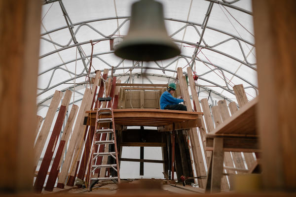A Mystic Seaport Museum shipwright works on Mayflower's restoration, seen through the ship's belfry.