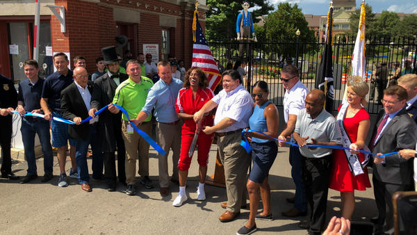 Gov. J.B. Pritzker, holding giant scissors, was frequently on his feet in August. Here he's seen at the ribbon-cutting for the Illinois State Fair.