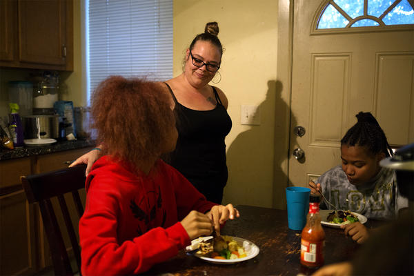Regina Hartfield speaks with her daughters Khia, 14, and Destinee, 12, as they eat dinner. Hartfield's children were dropped from Missouri's Medicaid program.