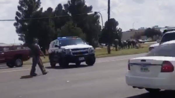 Police officers guard a street in Odessa, Texas, in this image made from video provided by Dustin Fawcett. A suspect killed and injured multiple people in a mass shooting on Saturday.