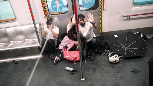 Police shoot pepper spray as they try to detain protesters inside a train at Prince Edward station in Hong Kong Saturday.