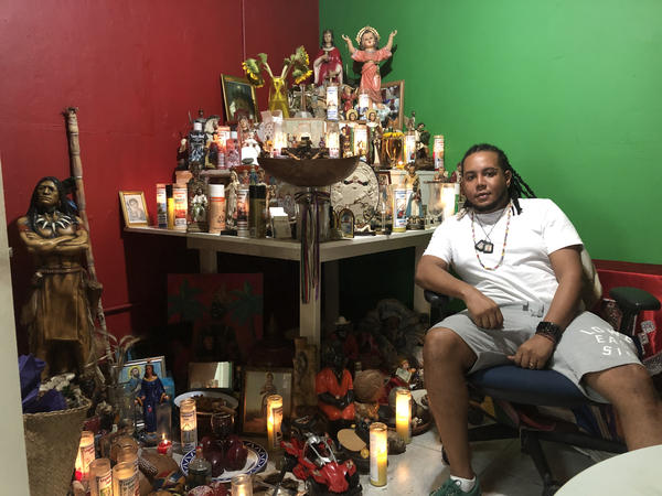 """Alex """"El Toleto"""" Escalante posing in front of his altar for the deities known as the mysteries, according to Dominican and Haitian religious traditions, inside of his business Botánica 21 División."""