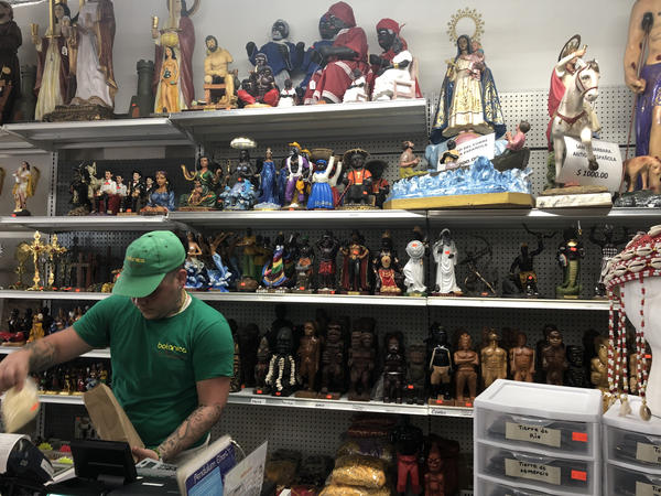 Luis Romero helping a customer in Botánica Nena in front of a range of saints.
