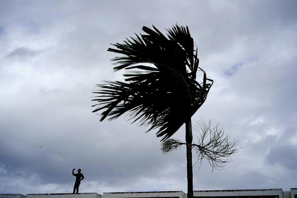 A man stands on a store's roof as he works to prepare it for the arrival of Hurricane Dorian on Sunday, Sept. 1, 2019. (Ramon Espinosa/AP)