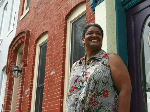 Jeanetta Churchill stands outside of her Baltimore row house. She says she has to keep her air running constantly in the summer in order to manage her bipolar disorder.