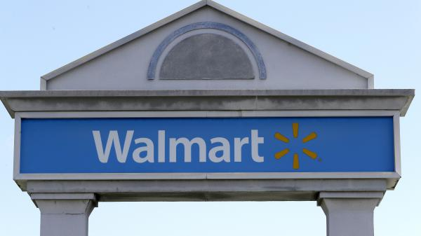 A Walmart logo forms part of a sign outside a Walmart store, Tuesday, Sept. 3, 2019, in Walpole, Mass. Walmart is going back to its folksy hunting heritage and getting rid of anything that's not related to a hunting rifle after a mass shooting this summer.
