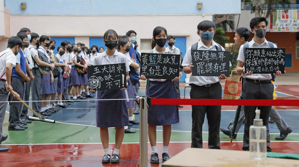 "High school students wearing masks hold placards that read ""Five key demands are indispensable"" as they continue their school boycott in Hong Kong on Wednesday."