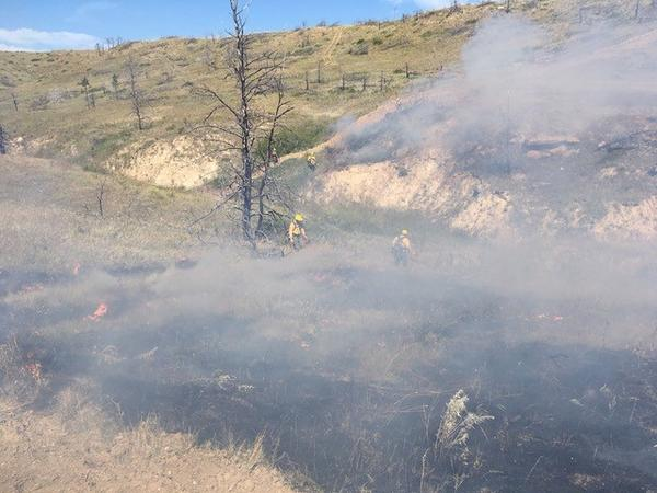 Fire fighers use drip torches to contain a grass fire ignited by a burning coal seam on the Northern Cheyenne Reservation over Labor Day weekend.