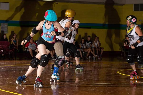 A photo from a Greensboro Roller Derby Game featuring John Xena with the red star on her helmet..