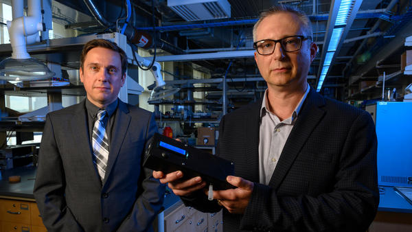 University of Pittsburgh researchers Ervin Sejdic and Alexander Star hold up their prototype Breathalyzer-style device for detecting THC — the main psychoactive ingredient in marijuana — in a person's breath.