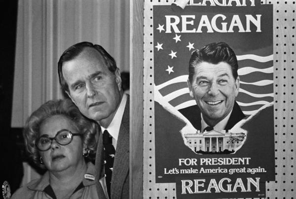 George H.W. Bush peeks at a poster of Ronald Reagan, then one of his opponents for the Republican party presidential nomination in 1980.  (AP file photo)