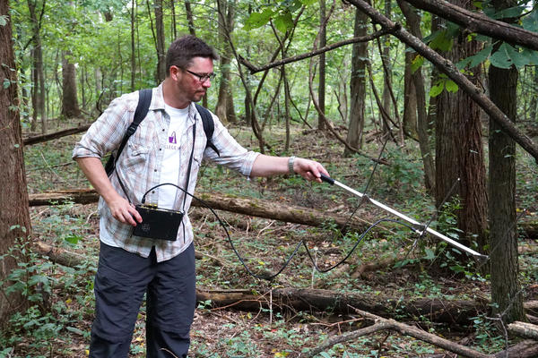 Ben Jellen, an associate professor of biology at St. Louis College of Pharmacy, uses a radio receiver to track a copperhead snake at Powder Valley Nature Center. Jellen is leading the study, which aims to better understand copperhead biology.