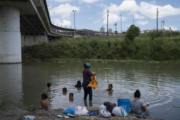 Asylum seekers that have been sent back under the 'Remain in Mexico' program bathe and wash clothes in the Rio Grande.