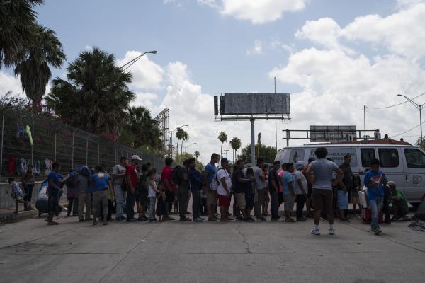 Asylum seekers wait in line to for ice cream near the Gateway International Bridge in Matamoros.