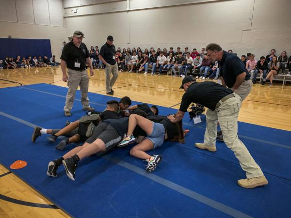 Students learn how to take down an active shooter as part of a three-part training program focused on 'evacuate, barricade, fight.'