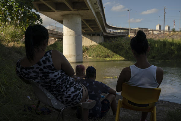 A group of asylum seekers, who are part of the LGBTQ community, sit near the Gateway International Bridge in Matamoros.