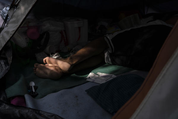 An asylum seeker rests in a tent near the Gateway International Bridge.