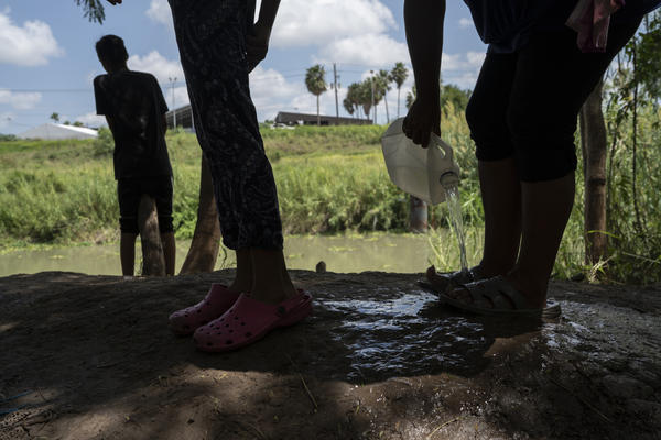 Asylum seekers rinse their feet after taking a bath in the Rio Grande.