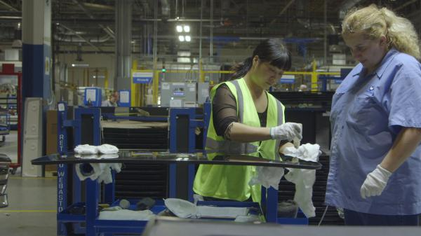 Yuzhu Yang (left) trains Lori Cochran at the Fuyao Glass America factory in Dayton, Ohio, in the documentary <em>American Factory.</em>