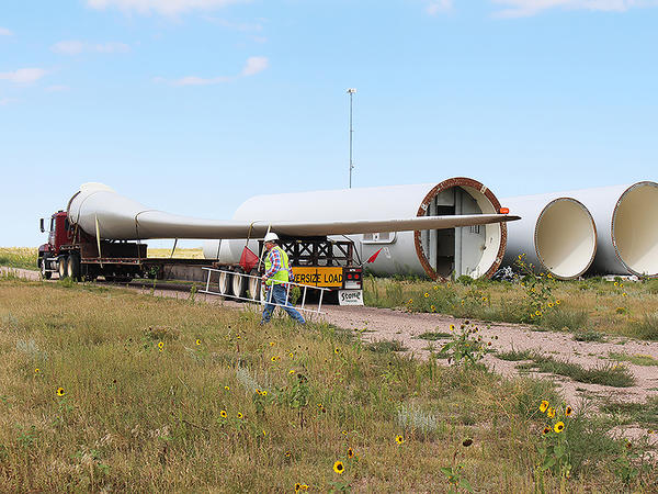 Rob Van Vleet secures a wind turbine blade onto an oversize truck at the Kimball Wind Farm in southwest Nebraska.