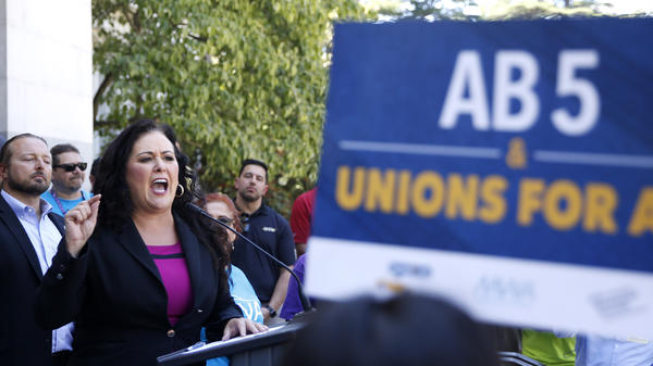 Democratic Assemblywoman Lorena Gonzalez speaks at a July rally for independent contractors in Sacramento, Calif. The measure that passed Tuesday in the state Senate requires companies such as Lyft and Uber to turn many of its contract workers into full employees.