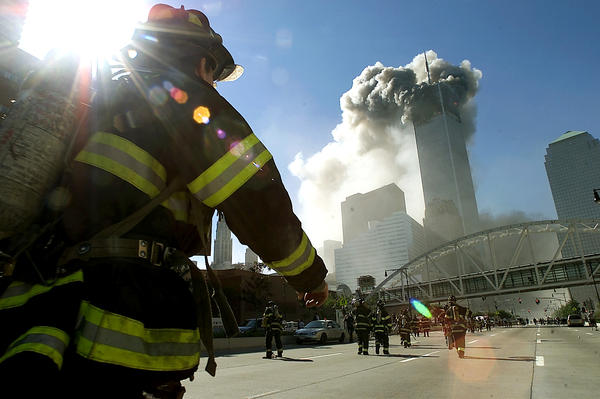 Firefighters walk towards one of the tower at the World Trade Center before it collapsed after a plane hit the building on September 11, 2001.