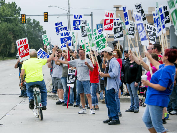 Demonstrators wave at a cyclist riding past during a United Auto Workers strike outside the General Motors Co. Flint Assembly plant in Flint, Mich., on Monday.