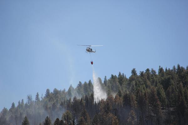 A helicopter drops water on the Bannack Fire, July 25, 2019.