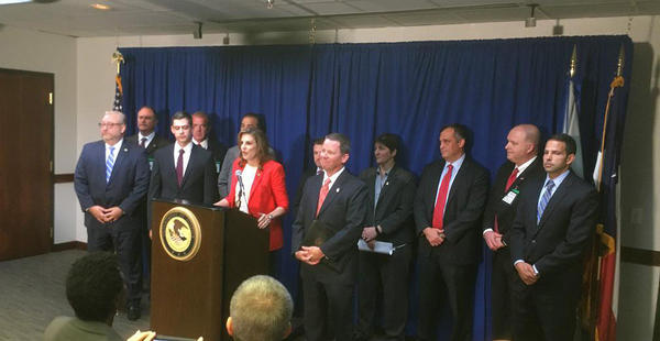 "Erin Nealy Cox, U.S. Attorney for the Northern District of Texas, talks of the ""massive takedown"" of alleged health care fraudsters. She's surrounded by officials from the FBI, DEA, IRS, Veterans Affairs and other federal agencies."