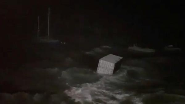 A cargo container is rocked by waves as Hurricane Humberto hits Hamilton, Bermuda, on Wednesday, in this still picture obtained from social media video.